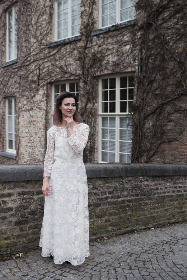 Huwelijksfoto het schieten Bruid die in Brugge lopen Tribune op brug en omhelzing stock foto