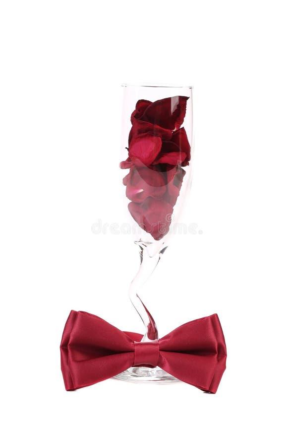 Huwelijksglas met rode roze bloemblaadjes stock foto's