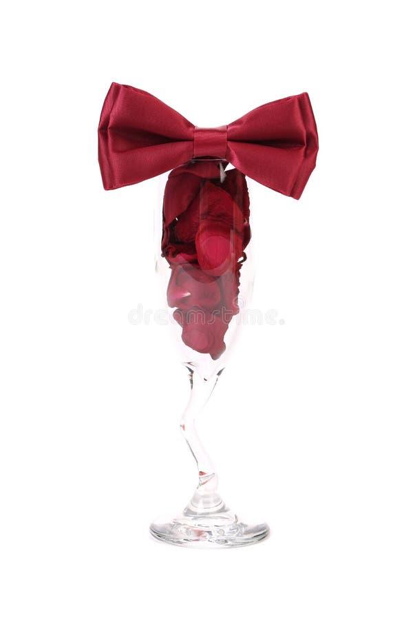 Huwelijksglas met rode roze bloemblaadjes. stock afbeelding