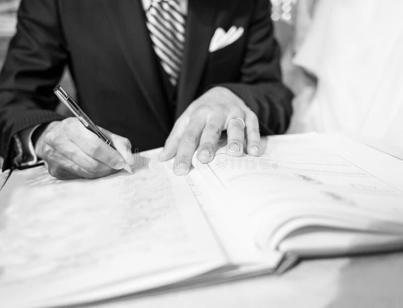 Huwelijkshandtekening tijdens de huwelijksceremonie stock foto