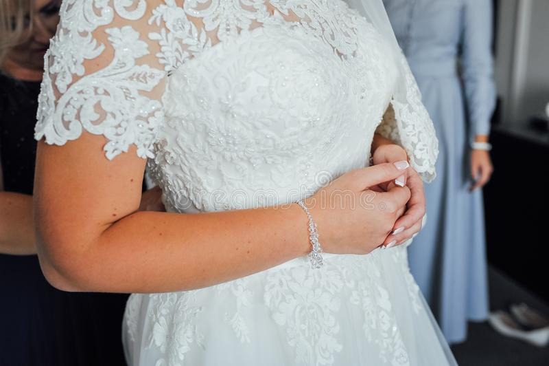 Huwelijkshulp Handen van bruidsmeisjes op bruids kleding Gelukkig huwelijk en bruid bij het concept van de huwelijksdag royalty-vrije stock afbeeldingen
