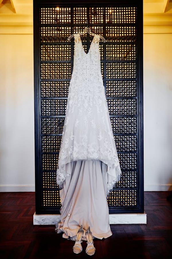 Huwelijkskleding het hangen op de muur met schoenen op de vloer, wolframlicht op achtergrond royalty-vrije stock afbeeldingen