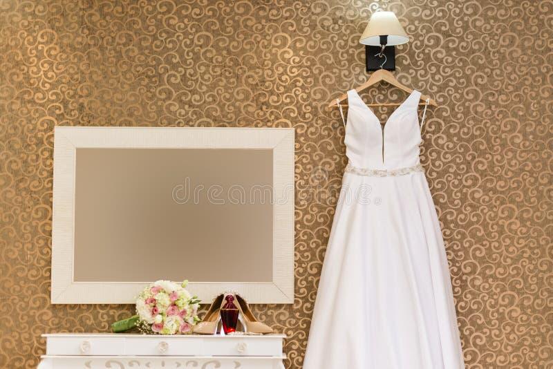 Huwelijkskleding het hangen op muur met textuur en bouque, parfum en juwelen royalty-vrije stock fotografie