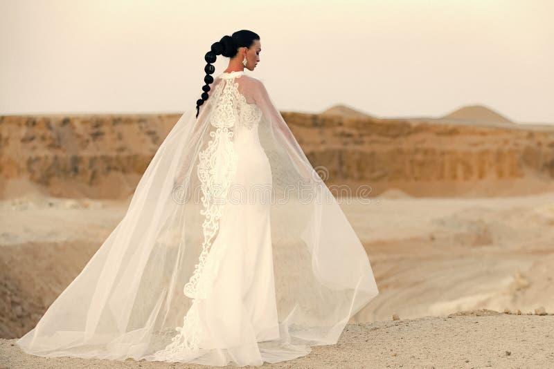 Huwelijkskleding Meisje het stellen in woestijn royalty-vrije stock foto