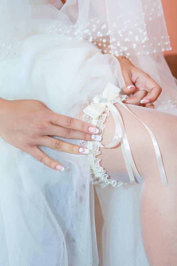 Huwelijkskouseband op het bruid` s been stock foto