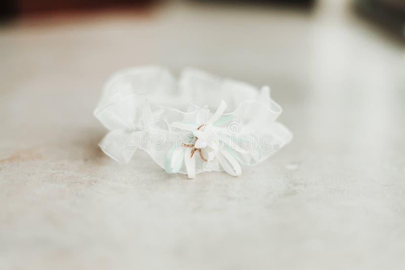 Huwelijkskouseband op witte bruids toebehoren als achtergrond stock foto