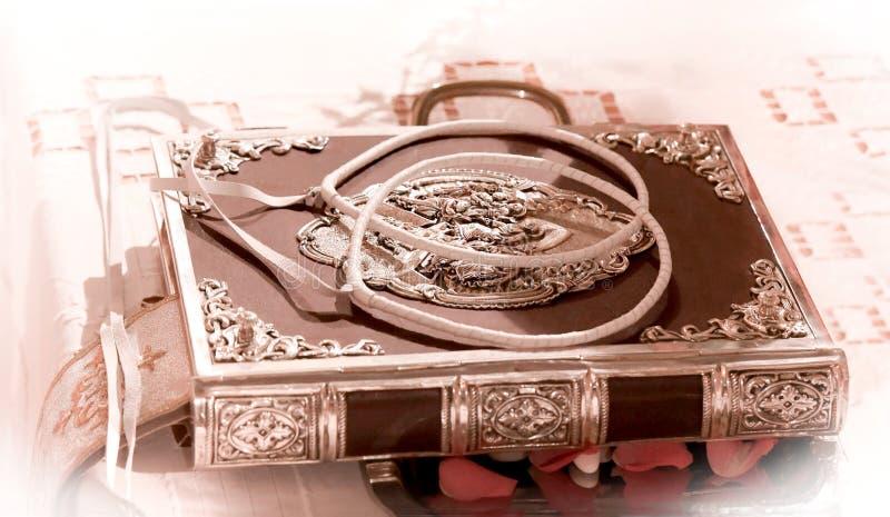 Huwelijkskronen op hulstbijbel op een evangelie wordt verfraaid die FO voorbereiden dat stock foto
