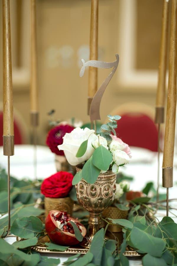 Huwelijkslijst het plaatsen is verfraaid met verse bloemen in een messingskom en gouden kaarsen in messingskandelaars Huwelijk royalty-vrije stock afbeelding