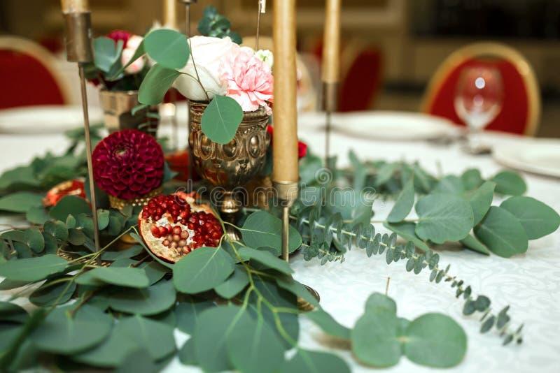 Huwelijkslijst het plaatsen is verfraaid met verse bloemen in een messingskom en gouden kaarsen in messingskandelaars Huwelijk stock fotografie