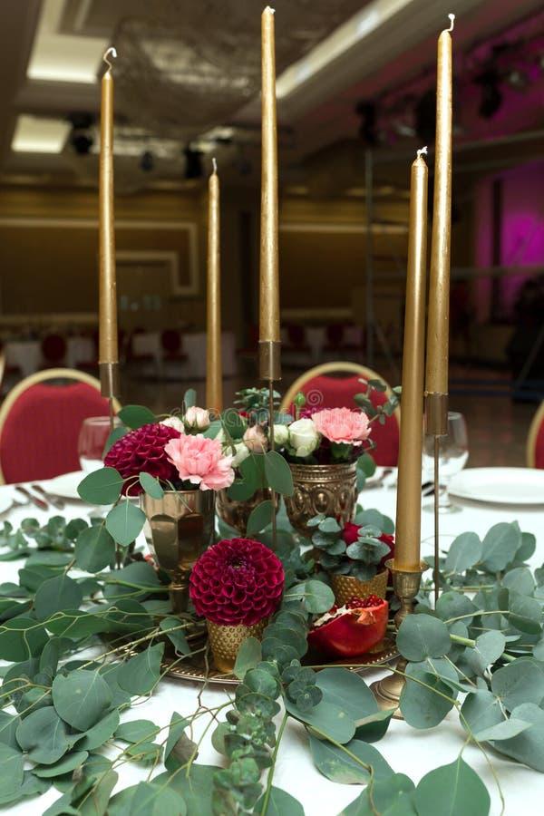 Huwelijkslijst het plaatsen is verfraaid met verse bloemen in een messingskom en gouden kaarsen in messingskandelaars Huwelijk stock foto's