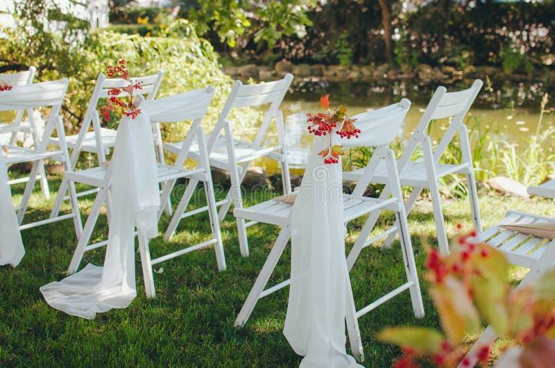 Huwelijksopstelling Ceremonie in de boezem van aard Witte die stoelen met bloemen in het gras worden geplaatst stock foto