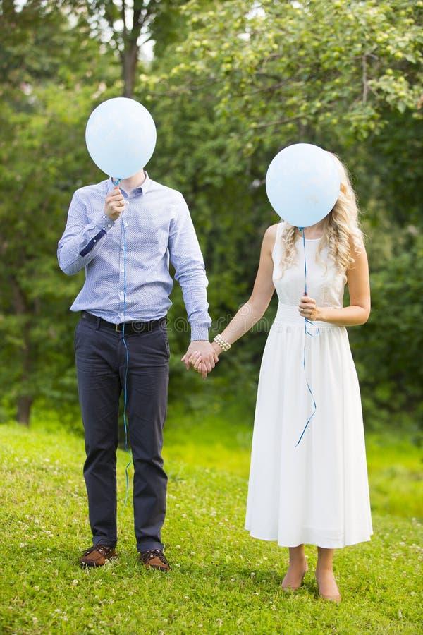 Huwelijkspaar - bruid en bruidegom - met blauwe ballons in plaats van hun gezichten stock afbeelding