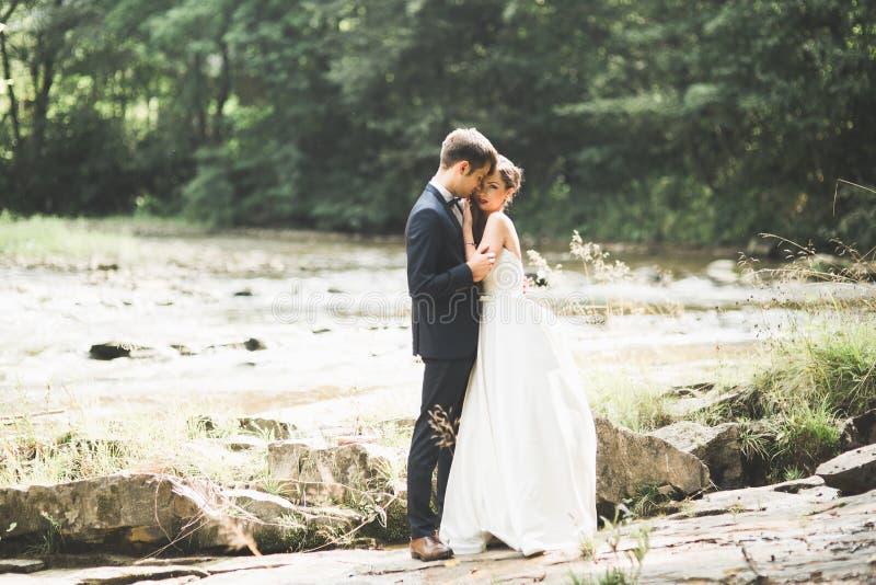 Huwelijkspaar, bruidegom en bruid die, openlucht dichtbijgelegen rivier koesteren stock fotografie