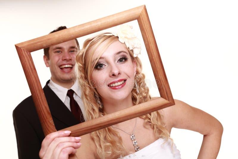 Huwelijkspaar in de bruidegom van de kader gelukkige bruid stock foto