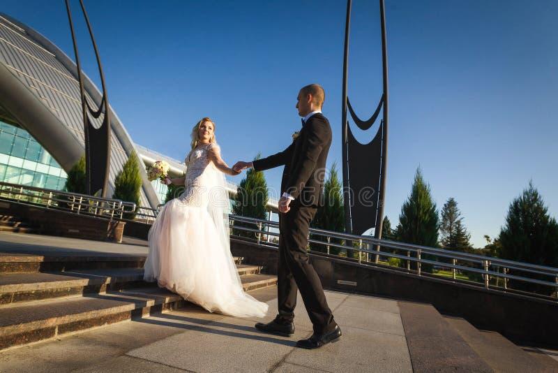 Huwelijkspaar die boven het moderne gebouw opheffen royalty-vrije stock foto's