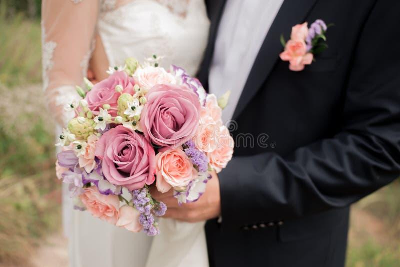 Huwelijkspaar die, de bruid die een boeket van bloemen in haar hand, bruidegom het omhelzen houden koesteren stock afbeeldingen