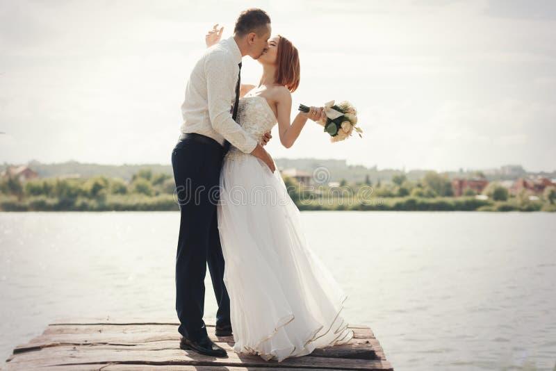 Huwelijkspaar die op brug dichtbij meer op zonsondergang bij huwelijksdag lopen Bruid en Bruidegom in Liefde stock foto's