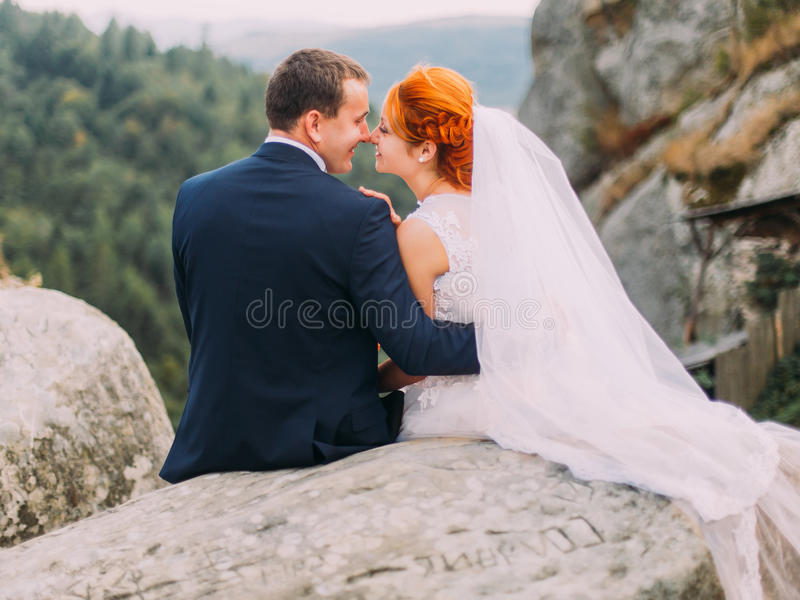 Huwelijkspaar die zacht bij rotsachtige bergen tegen de hemel omhelzen Leuk romantisch ogenblik royalty-vrije stock foto's
