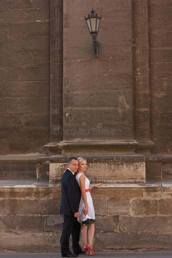 Huwelijkspaar die zich dichtbij de muur bevinden royalty-vrije stock fotografie