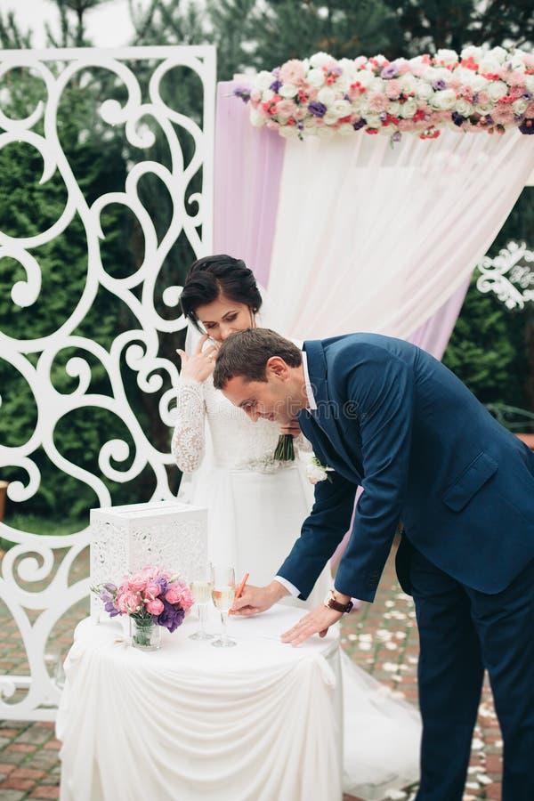Huwelijkspaar die zich onder een boog van verse bloemen bevinden royalty-vrije stock foto's
