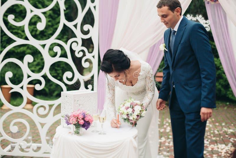Huwelijkspaar die zich onder een boog van verse bloemen bevinden royalty-vrije stock afbeeldingen