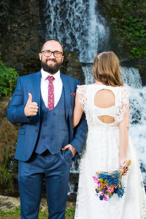 Huwelijkspaar die zich voor een waterval bevinden stock fotografie