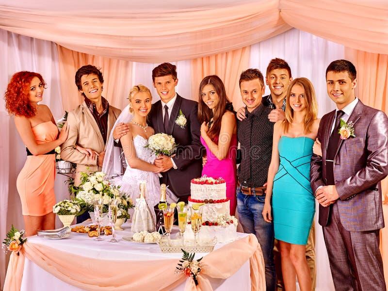 Huwelijkspaar en gasten die champagne drinken stock fotografie