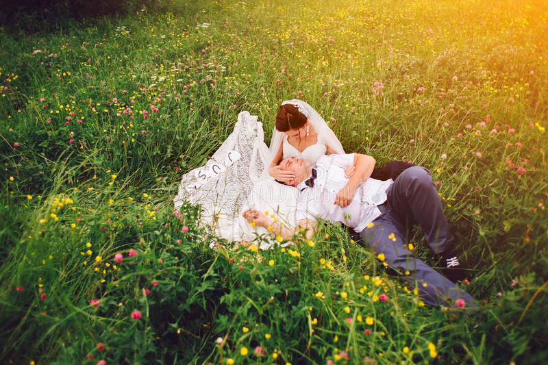 Huwelijkspaar in liefde op het hoogtepunt van de zonsondergangweide van bloemen stock afbeeldingen