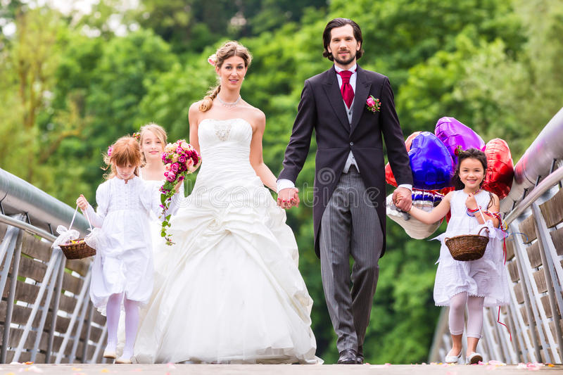 Huwelijkspaar met bloemkinderen op brug royalty-vrije stock afbeeldingen