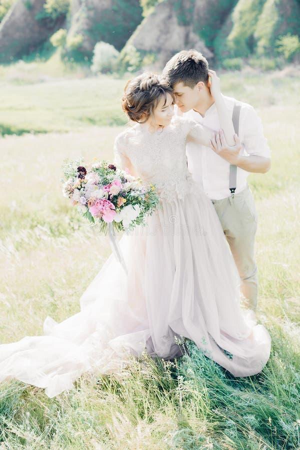 Huwelijkspaar op aard bruid en bruidegom die bij huwelijk koesteren royalty-vrije stock foto