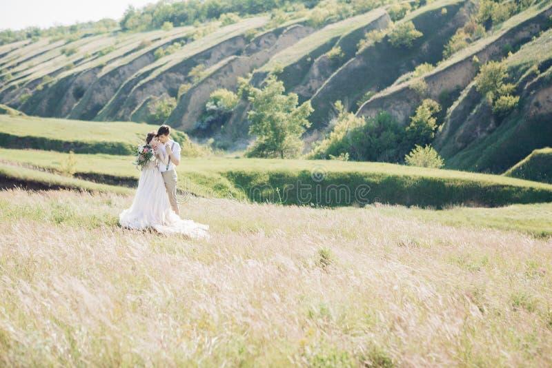 Huwelijkspaar op aard bruid en bruidegom die bij huwelijk koesteren stock foto