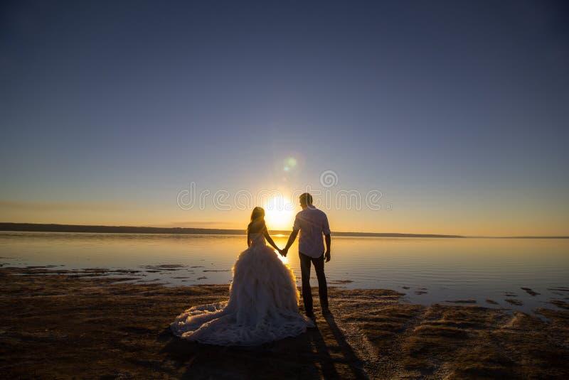 Huwelijkspaar op de het overzeese strand letten op zonsondergang Zonnige de zomerfoto Bruid met haar neer binnen van schouderkled royalty-vrije stock afbeeldingen