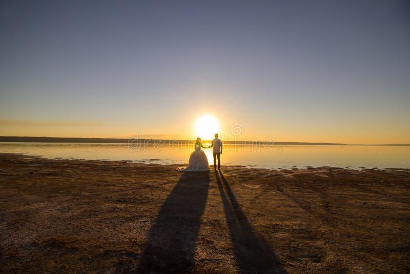 Huwelijkspaar op de het overzeese strand letten op zonsondergang Zonnige de zomerfoto Bruid met haar neer binnen van schouderkled royalty-vrije stock foto