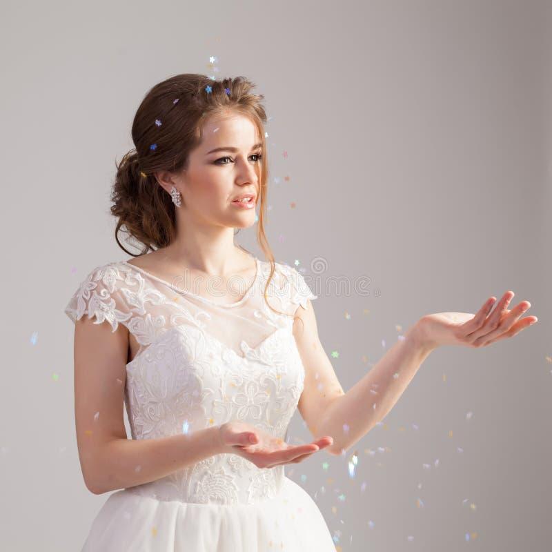 Huwelijkssamenstelling, kapsel en kleding De jonge krullende bruid stelt in studio op grijze achtergrond royalty-vrije stock foto