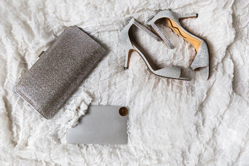 Huwelijksschoenen, beurs en kouseband op een grijze achtergrond stock foto