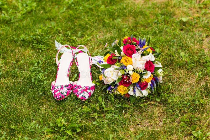 Huwelijksschoenen en bruids boeket stock foto's