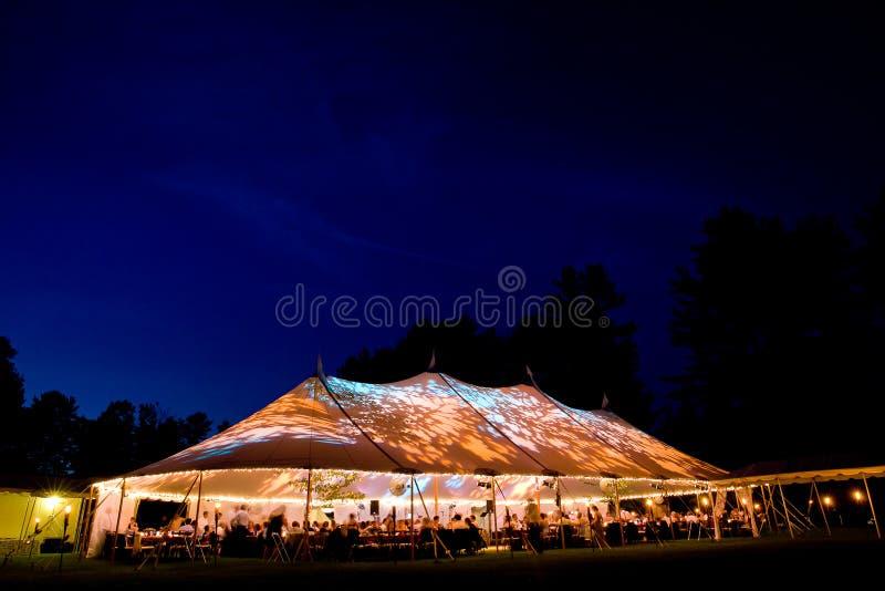 Huwelijkstent bij nacht - de Speciale gebeurtenistent stak omhoog van de binnenkant met donkerblauwe nachthemel en bomen aan stock foto's