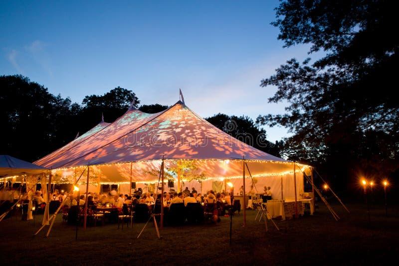 Huwelijkstent bij nacht - de Speciale gebeurtenistent stak omhoog van de binnenkant met schemerhemel en bomen aan stock afbeelding