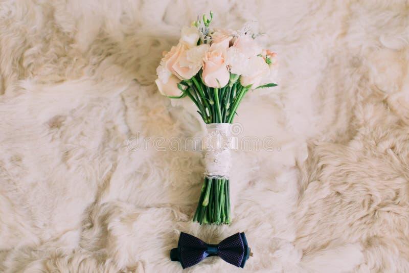 Huwelijkstoebehoren: blauwe vlinderdas van bruidegom, bruids rozenboeket op het witte bont stock foto