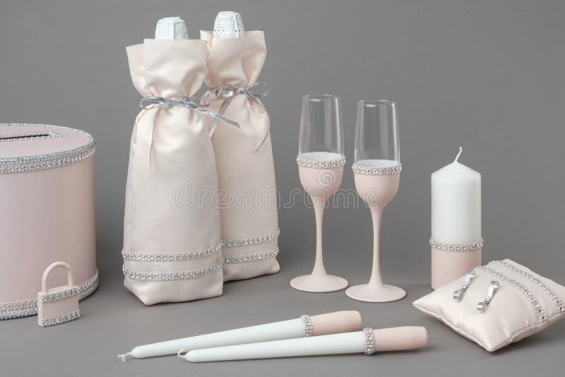 Huwelijkstoebehoren: flessen champagne in zakken, wijnglazen, kaarsen, doos voor geld, huwelijksslot en hoofdkussen voor ringen royalty-vrije stock afbeelding