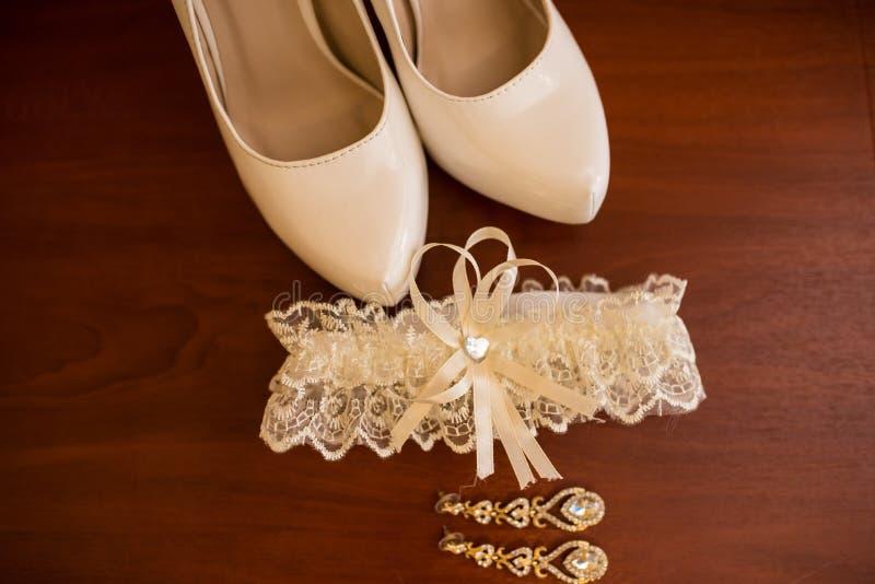 Huwelijkstoebehoren voor bruidschoenen, oorringen en kouseband stock fotografie