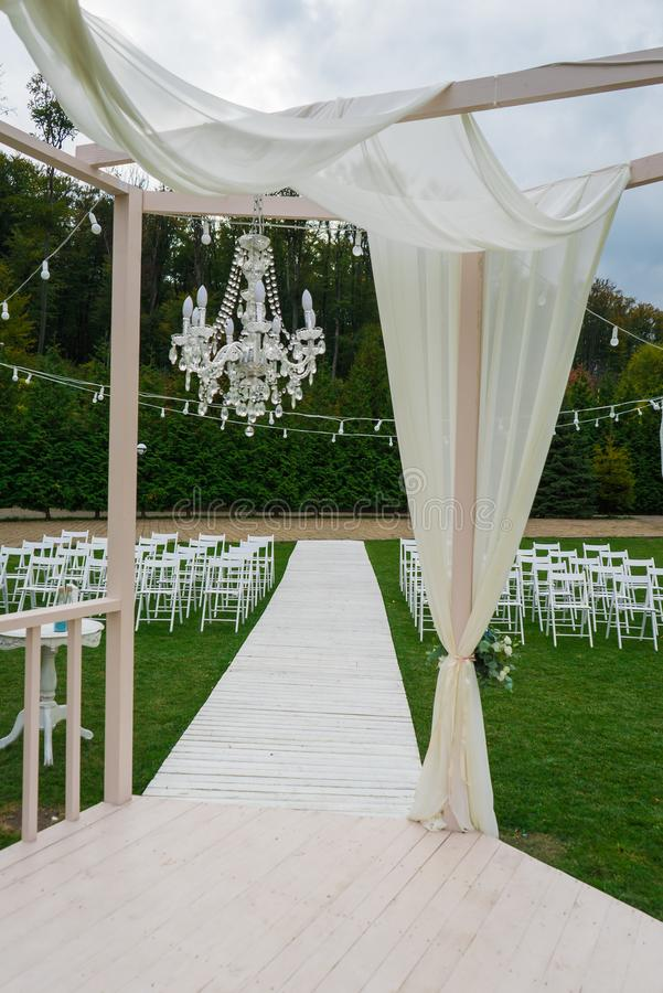 Huwelijkstrefpunt Witte stoelen op groen gras met nachtlichten Huwelijksopstelling Huwelijk het plaatsen Portretfoto spruit stock fotografie