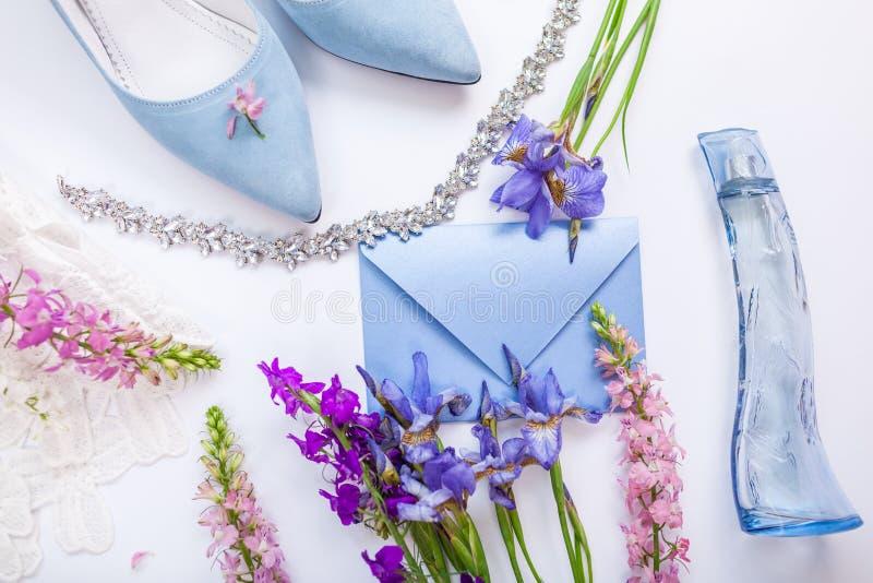Huwelijksuitnodiging met bloemen, de schoenen van de bruid, parfum en juwelen wordt omringd die Ochtend van bruid stock foto's