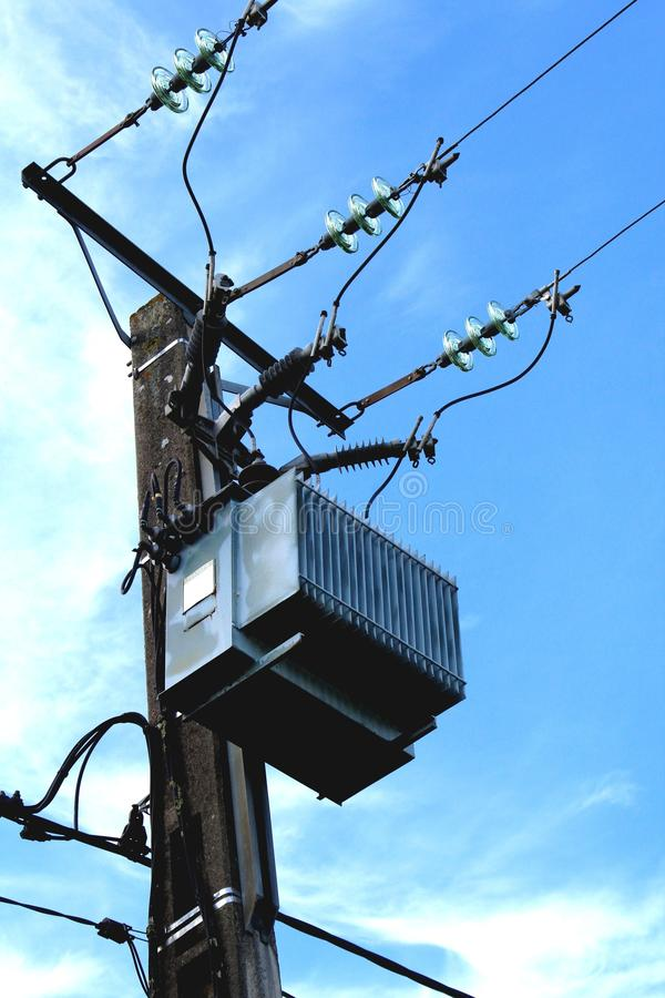 HV transformer. Posed on a pole in the countryside against the surface royalty free stock image