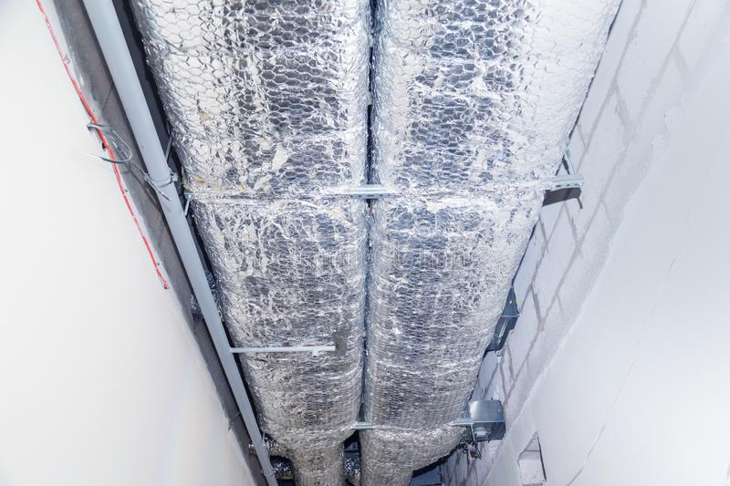 HVAC Duct Cleaning, Ventilation pipes in silver insulation material hanging from the ceiling inside new building royalty free stock photo