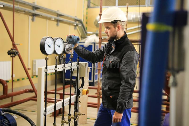 HVAC engineer in boiler room monitoring pressure gauges. Technician working on industrial plant royalty free stock photography