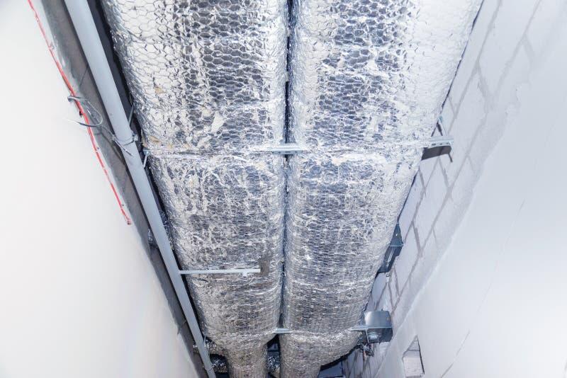 HVAC leiten Reinigung, Lüftungsrohre im silbernen Isoliermaterial, das von der Decke innerhalb des Neubaus hängt lizenzfreies stockfoto
