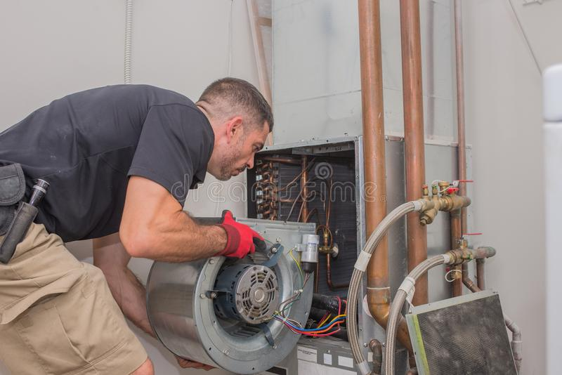 Hvac technician with Motor. Hvac repair technician removing a blower motor from air handler stock photography