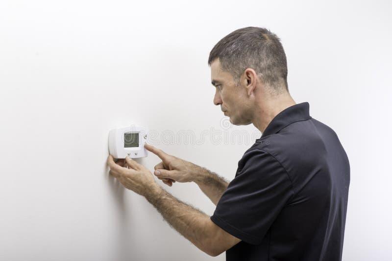 Hvac-Repairman Adjusting Thermostat arkivbilder