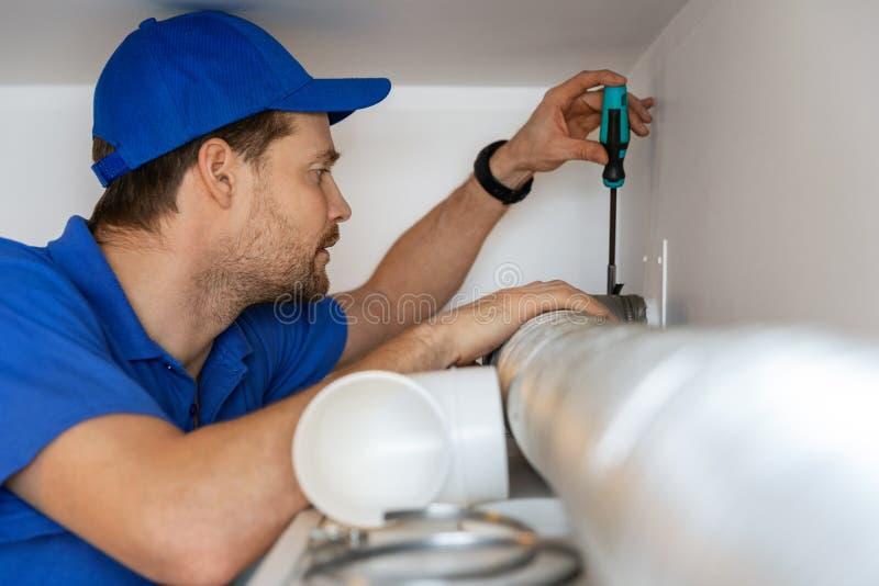 Hvac technician repairing flexible aluminum tube for house ventilation system royalty free stock photo